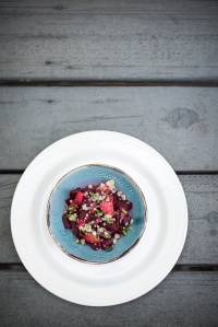 A blue bowl on top of a plain white plate that holds the braised beets with apple and bleu cheese.