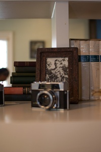 An old black and white photo in a rusted picture frame behind a vintage camera.