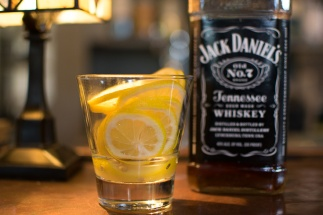 A glass of lemon slices and a bottle of Jack Daniel's Whiskey.