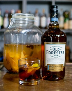 A Tumblr and bottle of Old Forester Kentucky Whisky sit on a bar.