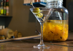 A martini class with two green olives sits on the bar.