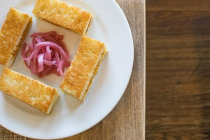 Three small rectangular sandwiches edge a white plate with pickled onion at its center.