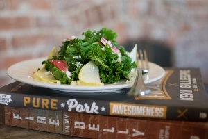A kale salad adorned with feta cheese and radish sits on top of two books.