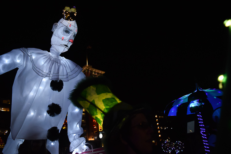 A tall white clown lantern towers over the parade.
