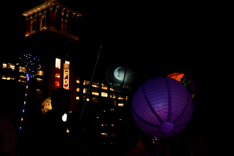 A purple lantern and a lantern with a moon illuminate the sky as the last lanterns to pass by Ponce City Market.