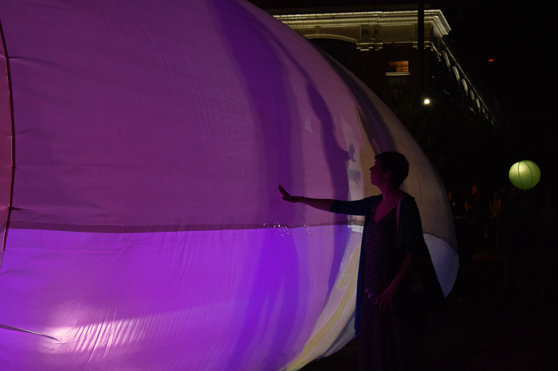 A girl with an outstretched arm, touches the lantern tent which is bathed in purple light.