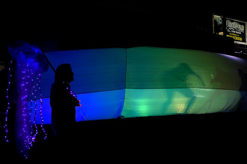 A man walks by the lantern tent carrying a lantern jellyfish that glows a deep indigo.