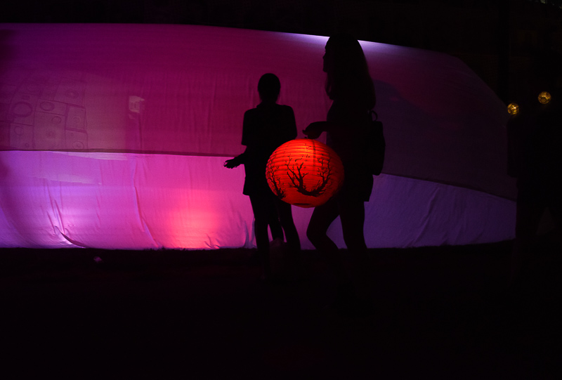 A girl, silhouetted against the backdrop of the lantern tent, carries a red lantern.