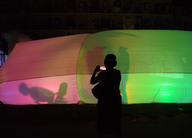 A parade goer takes video of the lantern tent which is bathed in pink and green light. Silhouettes can be seen.