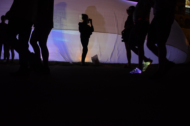 A man, silhouetted, walks by the lantern tent with glowing shoes.
