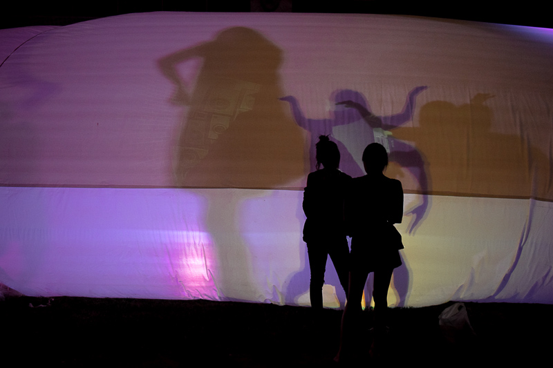 Two girls pose for photos in front of the lantern tent as silhouettes from the inside can be seen dancing.