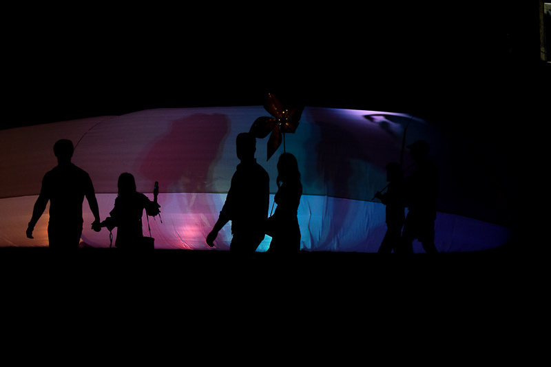 Figures walk in front of the lantern tent.